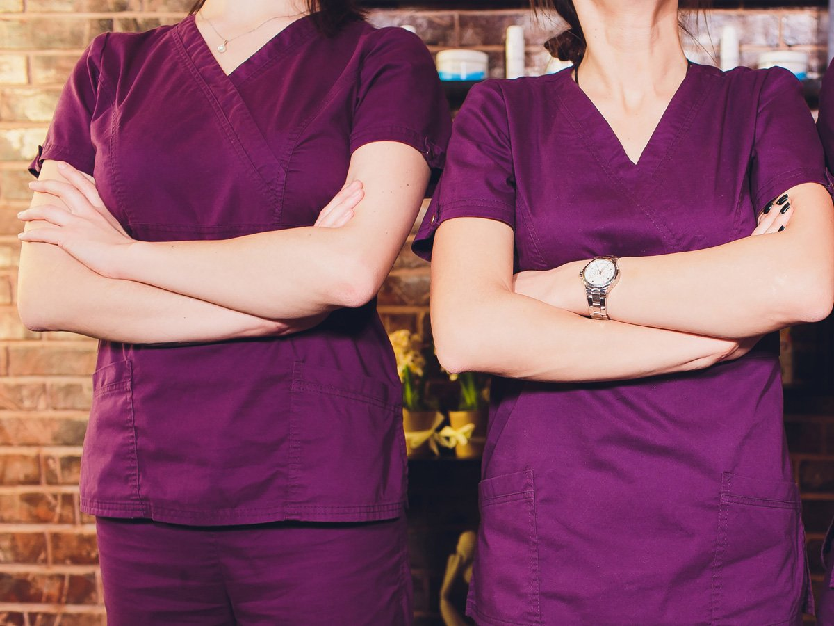 Portrait of female brunette cosmetologist in uniform in the cosmetology office three young women